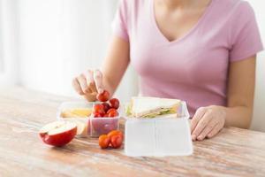 close up van vrouw met voedsel in plastic container foto