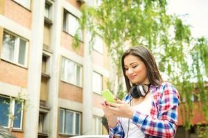 mooie tiener met slimme telefoon en koptelefoon buitenshuis