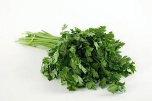 groene bladeren van peterselie geïsoleerd op een witte achtergrond foto