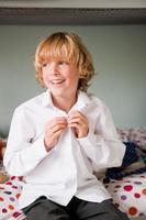 jonge jongen doet de knoppen van zijn school shirt zittend op zijn bed foto