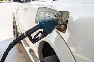 vul de witte auto met strijd aan de benzine bij foto