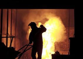 man aan het werk in het spatten gesmolten ijzer - stock beeld foto