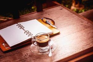 notitieboekje en koffiekop op oude houten achtergrond, bedrijfsconce foto