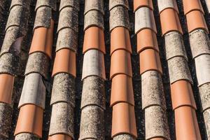 nieuwe terracotta tegels geplaatst op een verweerd dak