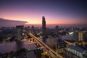 bangkok stad bij avondschemering met modern gebouw en brug foto