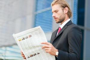 knappe zakenman die een krant leest foto