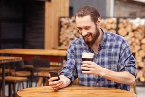 aantrekkelijke jonge kerel gebruikt telefoon in bierhuis foto