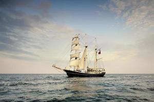 groot schip onder zeil met de kust op de achtergrond foto