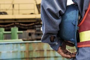 bouwvakker die plaatsplaats met kraan op de achtergrond controleert foto