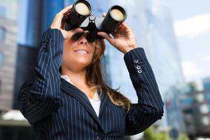 carrièrevrouw die met verrekijkers in de stad kijkt foto