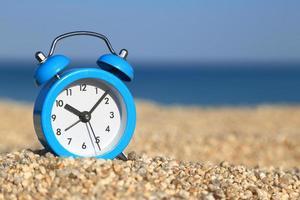 vakantietijd. wekker op het strand
