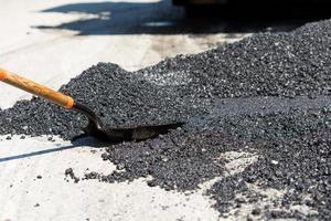 schop voor bouwwerkzaamheden in een hoop nieuw asfalt foto
