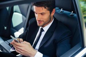 zakenman die smartphone in auto gebruiken foto
