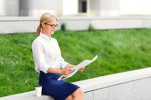 aangename vrouw die krant leest foto