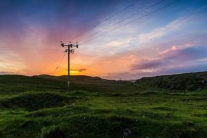 telefoon of elektriciteitslijn in de velden bij zonsondergang foto