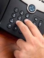 hand bellen nummer op zwarte vaste telefoon foto