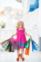 klein meisje met boodschappentassen gaat naar de winkel foto