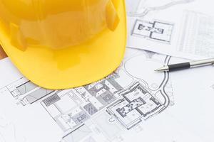 close up gele veiligheidshelm en plattegrond tekeningen foto