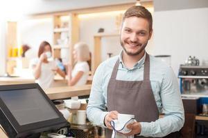 knappe jonge mannelijke barista is serviesgoed in café wassen foto