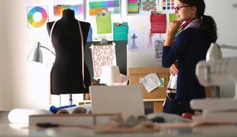 mooie modeontwerper permanent in studio foto
