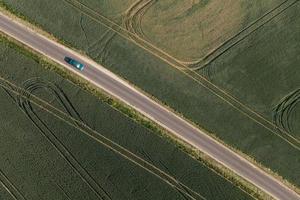 luchtfoto van dorpsweg en oogstvelden foto