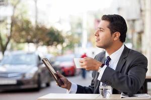 knappe man met pak gebruikt laptop in café foto