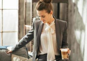 zakenvrouw met koffie latte in loft appartement foto