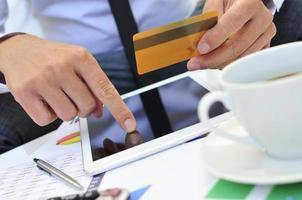 jonge man in pak online winkelen via een tablet-computer foto