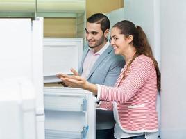 tevreden paar kijken naar grote koelkasten foto