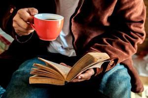 man een kopje koffie drinken en een boek lezen. foto