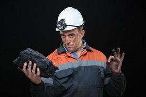 mijnwerker houdt een groot stuk energierijke kolen voor