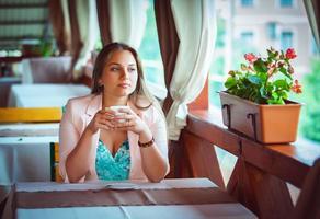 jonge aantrekkelijke vrouw genieten van een kopje koffie in het café foto