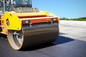asfaltwals zet een nieuwe weg foto