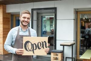knappe jonge barista maakt reclame voor zijn cafetaria foto