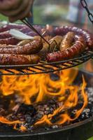 verschillende worstjes op de grill roosteren met open vuur foto