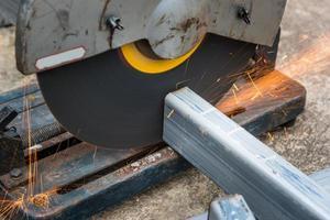 het zagen van een vierkant metaal en staal met een verstekzaag foto