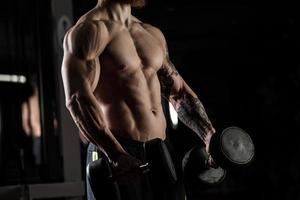 bodybuilder met halters in een sportschool, oefenen met een halter foto