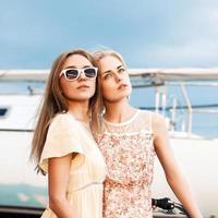 twee mooie meisjes op zee pier foto
