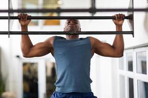 Afrikaanse man doet pull-ups op een balk foto