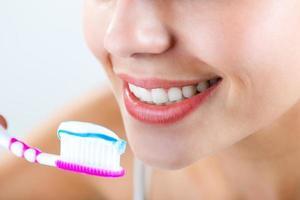 mooie jonge vrouw die zijn tanden plukt. foto