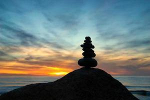 Cairn bij zonsondergang op de zee foto