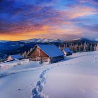 huisje in besneeuwde bergen met fantastische winterbomen