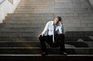 zakenman huilen verloren in depressie zittend op straat betonnen trappen