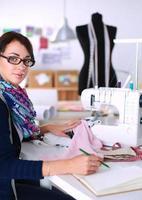 jonge vrouw naaien zittend op haar werkplek foto