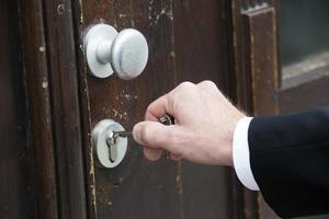 close-up van de hand met sleutel op een deur foto
