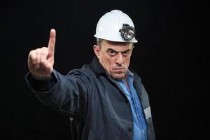 man met mijnwerker hoed en veiligheidskleding wijst vinger foto