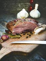 gerookt varkensvlees met kruiden, specerijen en mes op een houten bord. foto