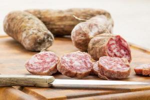 Italiaanse salami segmenten op snijplank met keukenmes foto