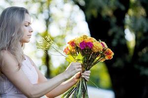 jonge mooie vrouwenbloemist. het meisje in het park tekent foto