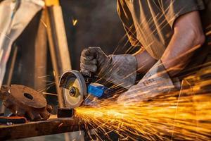 close-up van arbeider scherp metaal met molen foto